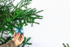 Una muchacha que cuelga una bola de la Navidad en un árbol de navidad en un fondo blanco Fotografía de archivo libre de regalías