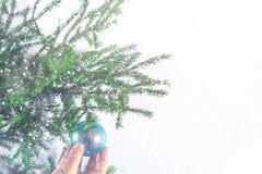 Una muchacha que cuelga una bola de la Navidad en un árbol de navidad en un fondo blanco Imagenes de archivo