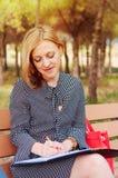 Una muchacha que descansa en un parque, en la hora de comer Una mujer en amor La mujer está pensando qué escribir imagen de archivo libre de regalías
