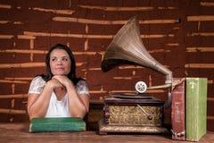 Una muchacha que escucha la música en un gramófono viejo Fotos de archivo