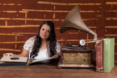 Una muchacha que escucha la música en un gramófono viejo Imagen de archivo