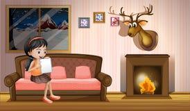 Una muchacha que estudia dentro de la casa cerca de la chimenea Foto de archivo libre de regalías