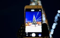 Una muchacha que fotografía un árbol de navidad en una cámara del smartphone, ciudad, Año Nuevo de los días de fiesta foto de archivo