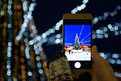 Una muchacha que fotografía un árbol de navidad en una cámara del smartphone, ciudad, Año Nuevo de los días de fiesta fotos de archivo