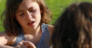 Una muchacha que habla con la muchacha de B en un jardín almacen de metraje de vídeo