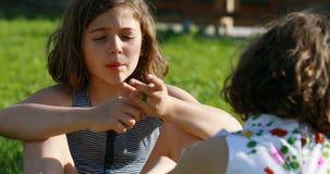 Una muchacha que habla con la muchacha de B en un jardín almacen de video