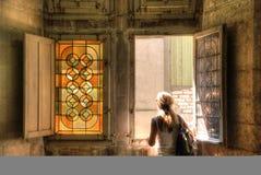 Una muchacha que hace frente cerca de una ventana de cristal manchada imágenes de archivo libres de regalías