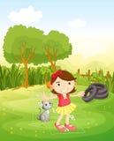 Una muchacha que juega en el parque con su gato Foto de archivo libre de regalías