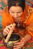 Una muchacha que juega en la taza tibetana de los sonidos Fotografía de archivo libre de regalías