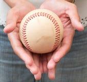 Una muchacha que lleva a cabo béisbol en la mano dos Foto de archivo