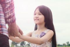Una muchacha que lleva a cabo las manos con el padre, vintage filtra Foto de archivo
