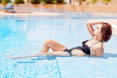 Una muchacha que miente en una piscina relajada. El vacaciones. Foto de archivo