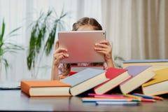 Una muchacha que mira la tableta Foto de archivo