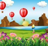 Una muchacha que mira los globos flotantes Imagenes de archivo