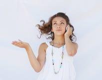 Una muchacha que mira para arriba mientras que en el teléfono celular. Fotografía de archivo libre de regalías