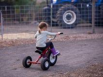 Una muchacha que monta una bici del triciclo con neumáticos grandes imágenes de archivo libres de regalías