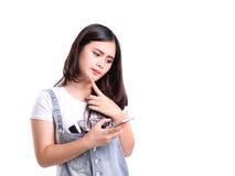 Una muchacha que piensa seriamente mientras que sostiene un teléfono móvil Imágenes de archivo libres de regalías