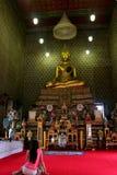 Una muchacha que ruega el templo real interior del monasterio Foto de archivo libre de regalías