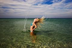 Una muchacha que salpica la agua de mar con su pelo Fotos de archivo