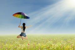 Una muchacha que salta con el paraguas Imágenes de archivo libres de regalías