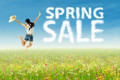 Una muchacha que salta con las nubes de la venta de la primavera Fotografía de archivo