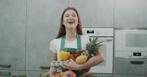 Una muchacha que se divierte en la cocina que lanza una pimienta en el aire metrajes