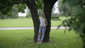 Una muchacha que se inclina sobre un árbol en un parque metrajes
