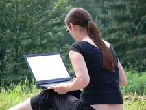 Una muchacha que se sienta afuera con una computadora portátil Imágenes de archivo libres de regalías