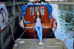 Una muchacha que se sienta al borde de un barco en el fondo del ol Foto de archivo