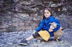 Una muchacha que se sienta en el monopatín y que sostiene la nave del juguete Imágenes de archivo libres de regalías