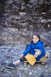 Una muchacha que se sienta en el monopatín y que sostiene la nave del juguete Foto de archivo libre de regalías
