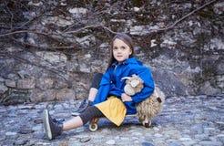 Una muchacha que se sienta en el monopatín y que sostiene la nave del juguete Imagen de archivo libre de regalías