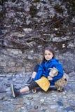 Una muchacha que se sienta en el monopatín y que sostiene la nave del juguete Foto de archivo