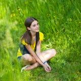 Una muchacha que se sienta en hierba verde imagenes de archivo