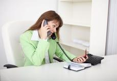 Una muchacha que se sienta en los escritorios y que habla en el teléfono Fotografía de archivo libre de regalías