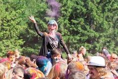 Una muchacha que se sienta en sus hombros en el individuo lanza una pintura seca en el festival en un grupo de personas grande Foto de archivo libre de regalías