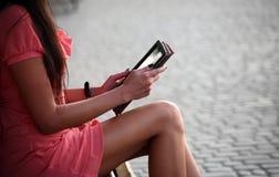 Una muchacha que se sienta en un banco y que lee un libro Fotos de archivo