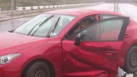 Una muchacha que se sienta en un coche quebrado despu?s de un accidente de tr?fico en un camino mojado bajo la lluvia metrajes