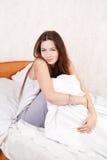 Una muchacha que se sienta en una cama Fotografía de archivo libre de regalías