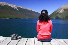 Una muchacha que se sienta por el lago Foto de archivo libre de regalías