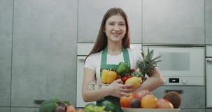 Una muchacha que sonríe llevando a cabo la fruta y el veg nutritivos almacen de video