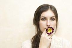 Una muchacha que sostiene la flor del primerose que finge fumar imagenes de archivo