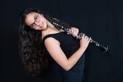 Una muchacha que sostiene su instrumento de música del clarinete Figura contra un fondo negro Imágenes de archivo libres de regalías