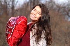 Una muchacha que sostiene un globo bajo la forma de corazón Fotos de archivo
