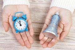 Una muchacha que sostiene un reloj y una campana El Año Nuevo o la Navidad está viniendo Concepto del Año Nuevo Fotografía de archivo libre de regalías