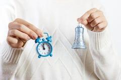 Una muchacha que sostiene un reloj y una campana El Año Nuevo o la Navidad está viniendo Concepto del Año Nuevo Imagen de archivo libre de regalías