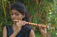 Una muchacha que toca la flauta Foto de archivo libre de regalías