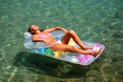 Una muchacha que toma el sol en un colchón Fotos de archivo