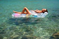 Una muchacha que toma el sol en un colchón Foto de archivo libre de regalías