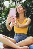 Una muchacha que toma un selfie en verano Imagenes de archivo